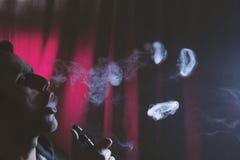 Молодой человек куря электронную сигарету или сигареты e стоковое изображение rf