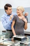 Молодой человек кладет ожерелье на его подругу Стоковые Изображения