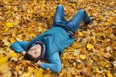 Молодой человек кладя в листву. Стоковые Изображения