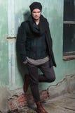 Молодой человек моды держит ногу на старой стене Стоковое фото RF