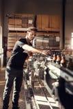Молодой человек наблюдая процесс пива разливая по бутылкам Стоковое Изображение RF
