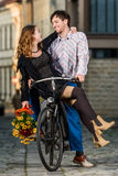Молодой человек нажимая его подругу на велосипеде Стоковая Фотография