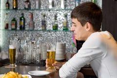 Молодой человек наслаждаясь стеклом пива с другом Стоковое Фото