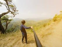 Молодой человек на верхней части горы фотографируя с камерой на ручке selfie Стоковые Изображения RF