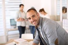 Молодой человек на деятельности офиса, коллеги в задней части Стоковая Фотография