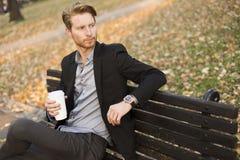 Молодой человек на кофе стенда выпивая на парке осени Стоковая Фотография RF