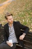 Молодой человек на кофе стенда выпивая на парке осени Стоковая Фотография