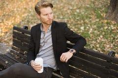 Молодой человек на кофе стенда выпивая на парке осени Стоковое фото RF