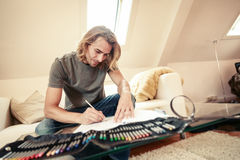 Молодой человек на кресле, рисуя в книжка-раскраске Стоковая Фотография
