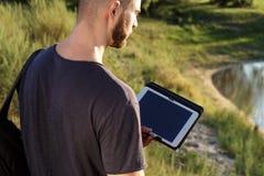 Молодой человек на походе в природе используя цифровую таблетку Стоковое фото RF