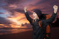 Молодой человек на предпосылке захода солнца моря поднял ее руки вверх и клекоты Стоковое Изображение RF