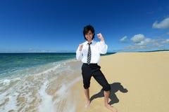 Молодой человек на пляже наслаждается солнечным светом стоковые фото