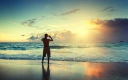 Молодой человек на пляже принимает фото стоковое фото rf