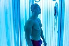 Молодой человек на солярии в салоне красоты Стоковые Фотографии RF