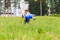 Молодой человек нося его подругу в его оружии на поле травы Соедините иметь потеху в природе на летний день Стоковое Фото