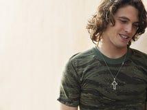 Молодой человек нося перекрестное ожерелье формы Стоковые Фото