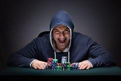 Молодой человек нося hoodie при карточки и обломоки играя в азартные игры стоковые изображения rf