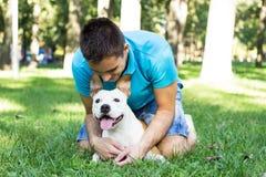 Молодой человек обнимая его собаку стоковые фотографии rf
