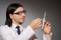 Молодой человек доктора с шприцем против Стоковая Фотография RF