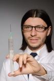 Молодой человек доктора с шприцем против Стоковые Изображения RF