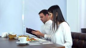 Молодой человек оплачивая счет пока его подруга проверяя ее телефон видеоматериал