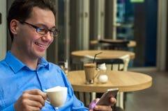 Молодой человек отправляя СМС в кафе Счастливый бизнесмен усмехаясь и отправляя СМС на smartphone на таблице стоковое фото