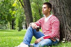 Молодой человек отдыхая с книгой и кофе для того чтобы пойти стоковое фото