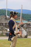 Молодой человек одетый как солдат, демонстрируя как мушкет нагружен и увольнян против врага, форта Ticonderoga, Нью-Йорка, 2014 Стоковые Фото