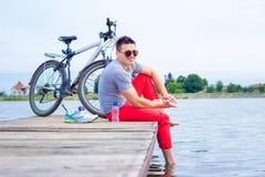 Молодой человек, одна счастливая туристская карта велосипедиста нося в серой рубашке при стекла сидя на пляже и отдыхая после езд Стоковые Изображения