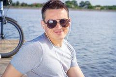 Молодой человек, одна счастливая туристская карта велосипедиста нося в серой рубашке при стекла сидя на пляже и отдыхая после езд Стоковое Изображение RF