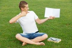 Молодой человек пишет к тетради Стоковое Изображение