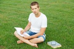 Молодой человек пишет к тетради Стоковые Фотографии RF