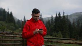 Молодой человек пишет SMS в вечере в горах Вокруг леса в тумане сток-видео