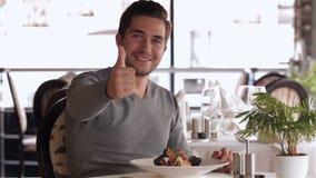 Молодой человек показывает большие пальцы руки вверх и усмехаться видеоматериал