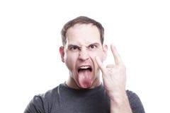 Молодой человек показывает язык знака руки рок-н-ролл стоковая фотография rf