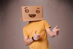Молодой человек показывать с картонной коробкой на его голове с smiley Стоковое Изображение RF