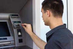 Молодой человек положил кредитную карточку на ATM стоковая фотография rf