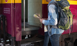 Молодой человек получает в международный поезд один с картой перемещения на платформе в железнодорожном вокзале Стоковое Изображение