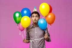 Молодой человек празднуя день рождения, держа красочные baloons над фиолетовой предпосылкой Стоковые Фотографии RF