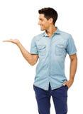 Молодой человек представляя незримый продукт стоковое изображение rf