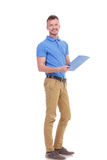 Молодой человек принимает примечания на доске сзажимом для бумаги Стоковое Фото
