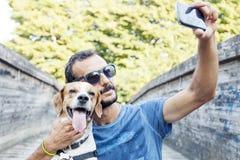 Молодой человек принимает selfie с его собакой стоковая фотография