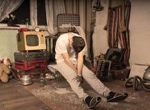 Молодой человек принимая ворсину на грязную покинутую комнату стоковые фотографии rf