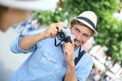 Молодой человек принимая фото его подруги Стоковое Изображение