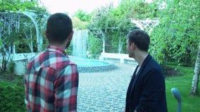 Молодой человек пришел навестить друг в курорте 2 друз говорят на фонтане в парке центра обработки сток-видео