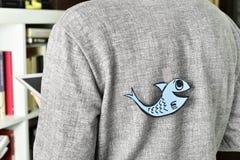 Молодой человек при бумажная рыба прикрепленная к его назад Стоковая Фотография