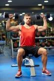 Молодой человек при гантели изгибая мышцы в спортзале Стоковые Фото
