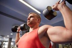 Молодой человек при гантели изгибая мышцы в спортзале Стоковые Изображения