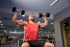 Молодой человек при гантели изгибая мышцы в спортзале Стоковое Изображение