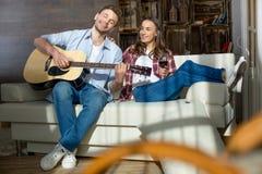 Молодой человек при закрытые глаза играя женщину гитары близко усмехаясь с бокалом Стоковые Изображения